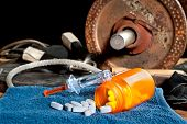 Steroid medication including pills and a syringe in front of exercise equipment.  Image can be used