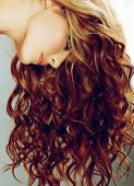 beautiful woman with long curly red hair on studio background