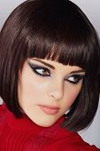 beautiful young woman with short brown hair in red blouse wearing smoky purple eyeshadow and dramati