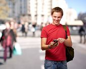 portrait of young man touching mobile screen at crowded street