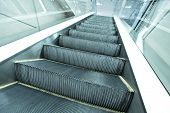 Wide long gray steps of quick moving escalator way in business passage, industrial motion background