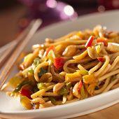 spicy thai noodles with chopsticks shot closeup
