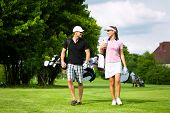 image of golf  - Young sportive couple playing golf on a golf course - JPG