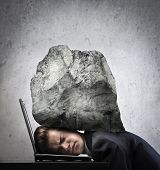 Young businessman with his head squeezed between a laptop keyboard and a rock