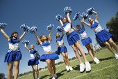 Group of excited young cheerleaders cheering on field
