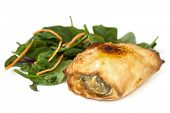 Chicken filo with a spinach salad, isolated on white background.