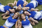 Group of happy young cheerleaders lying on field forming a circle