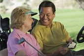 Happy man and woman with scorecard sitting in golf cart