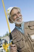 Happy Hispanic senior man looking away while holding fishing rod