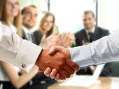 stock photo of negotiating  - handshake on the background of applause - JPG