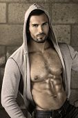 stock photo of hairy  - Young handsome macho man with open jacket revealing muscular chest and abs - JPG