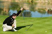 Comprimento total de um jovem golfista masculino alinhando putt nas proximidades do Lago