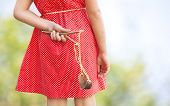 stock photo of prank  - Naughty girl hiding slingshot behind her back - JPG