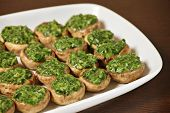 A picture od champignon mushrooms stuffed with spinach and served on a white plate over wooden backg