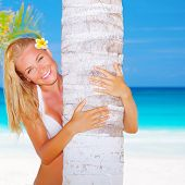 Sexy blond woman with frangipani flower in head hug palm tree on beautiful seascape background, luxury spa resort, enjoying summer vacation on the beach
