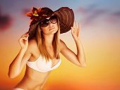 Seductive female on the beach, luxury model wearing stylish sunglasses and hat posing on beautiful o