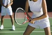 Midsection of mixed doubles tennis players on court with focus on woman