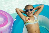 Portrait of a cheerful little girl lying on inflatable raft in swimming pool