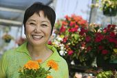 stock photo of marigold  - Portrait of a smiling middle aged woman with flowers in plant nursery - JPG