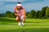 Young female golf player on course aiming for put