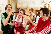 Young people in traditional Bavarian Tracht in restaurant or pub having fun and making jokes