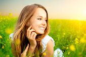 Beauty Girl in the Meadow. Beautiful Young Woman Outdoors. Enjoy Nature. Healthy Smiling Girl lying