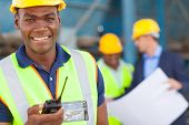 happy african american industrial worker with walkie talkie on site with colleagues