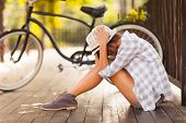 foto of broken heart flower  - sad young woman sitting at the park next to bicycle - JPG