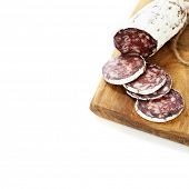 Close-up traditional sliced meat sausage salami on wooden board