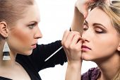 Backstage scène: professionele Make-up artiest glamour model make-up op het werk doen