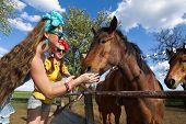 Beautiful girl feeding her horses at ranch