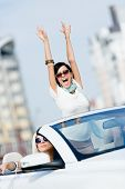 Lovely teenager with her hands up in the car with friends. Girls drive somewhere on vacation