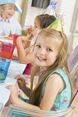 Young Girl At Party Sitting At Table With Food Smiling