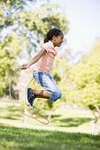 image of jump rope  - Young girl using skipping rope outdoors smiling - JPG