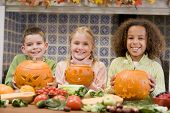 Three Young Friends On Halloween With Jack O Lanterns And Food Smiling