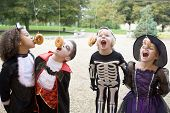 image of fancy-dress  - Four young friends on Halloween in costumes eating donuts hanging off strings - JPG