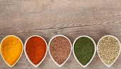 stock photo of flax seed  - Colourful ground or dried herbs and spices with copy space on the side - JPG