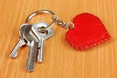 Key with leather trinket on wooden background