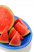 Closeup of a seedless watermelon on a blue platter. Half a melon surrounded by wedges of fruit. Vert