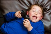 Young Boy Playing Video Game Laying On Couch At Home