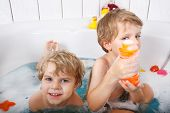 Two Little Twins Boys Having Fun With Water By Taking Bath In Bathtub.