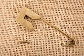 pic of brooch  - Vintage brooch or safety pin on jute background - JPG