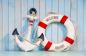 foto of anchor  - Anchor and life buoy on a background of white shabby wall boards - JPG