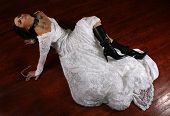 a woman on a stained floor in a wedding dress
