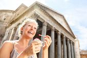 Girl eating ice cream by Pantheon, Rome, Italy. Happy tourist woman laughing enjoying Italian gelato