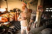 BHAKTAPUR, NEPAL - DEC 7, 2013:  Unidentified Nepalese man smokes  in his pottery workshop, Dec 7, 2
