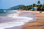 foto of tide  - Exiting Anjuna beach panorama on low tide with white wet sand and green coconut palms Goa India - JPG