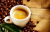 Coffee. Coffee Espresso. Cup Of Coffee with Beans and Green Leaf on a Wooden Background. Border Desi