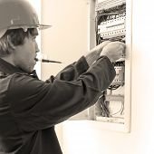 stock photo of fuse-box  - Young Electrician in protective helmet checking fuse box - JPG