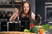 stock photo of apron  - Cheerful young woman in apron on modern kitchen will ladle tasting from pot - JPG